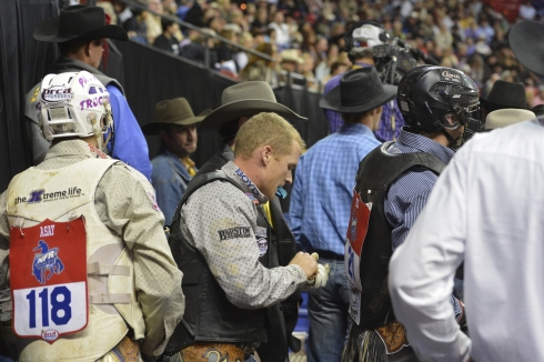 Kanin Asay, left, Tate Stratton, center, (preparing to put on his helmet) and Cody Teel are three of 13 Wrangler NFR bull riders wearing helmets.  (PRCA ProRodeo photo by Greg Westfall)