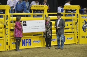 PRCA Commissioner Karl Stressman signed a check for $14.5 million, representing the amount raised by the rodeo industry for the Tough Enough To Wear Pink program, headed by Terry Wheatley, center.  (PRCA ProRodeo photo by Greg Westfall)